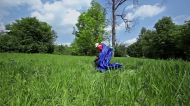Little boy pitches tent on grass glade under blue sky — Stock Video