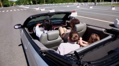 Parents and two kids sit in cabriolet and ride by road — Stock Video