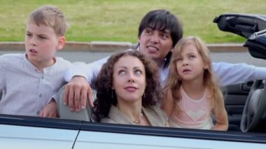 Parents and two kids sit in cabriolet and watch upward — Stock Video