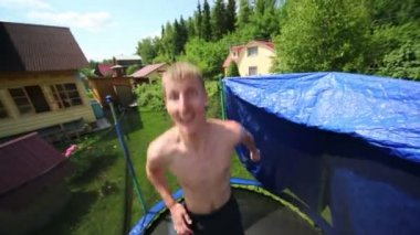 Man jumps and raises hands to sides on trampoline — Stock Video
