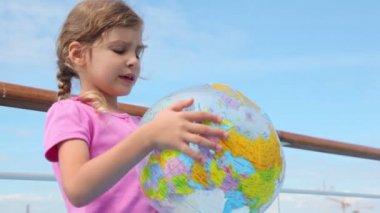 Liten flicka håller uppblåst boll och läser högt nära räcke — Stockvideo