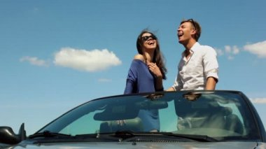 Young couple in sunglasses stand on cabriolet and look at sun — Stock Video