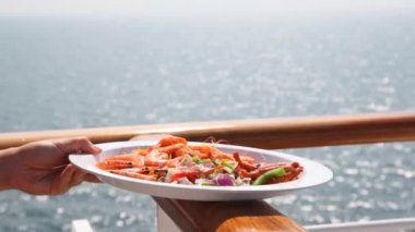 Hand holds plate with seafood and salad on handrail against sea — Stock Video
