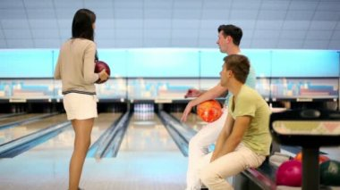 Two boys watch how girl makes throw in bowling game — Stock Video