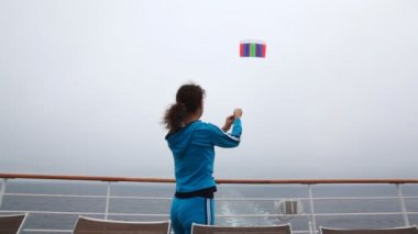 Woman flies multi-colored kite in gray sky from ship deck — Stock Video