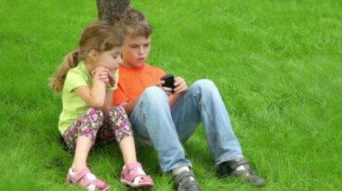 Dwoje dzieci siedzą razem w trawy w pobliżu drzewa — Wideo stockowe