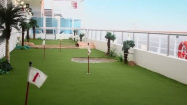 Field for mini golf on deck of ship which float on wavy sea — Stock Video