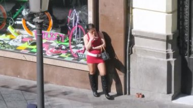Young girl in red dress stands near shop show-window on street — Stock Video