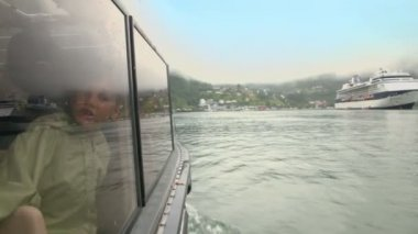 Girl talk behind window of rescue boat which float to huge liner — Stock Video