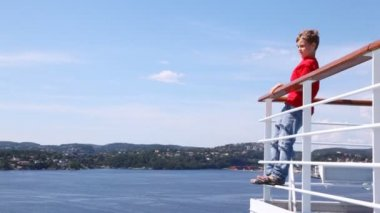 Boy waves greeting by hand standing on ship handrail — Vidéo