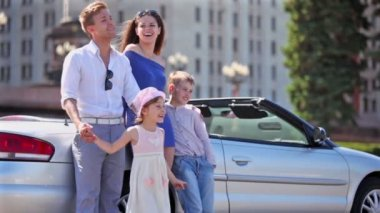 Couple and kids stand near cabriolet, boy hold girl — Stock Video