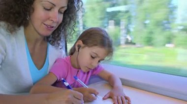 Little girl and mother draw by pens in book when sit at train — Stock Video