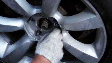 Hands in glove screw up nuts on car wheel, closeup view — Stock Video