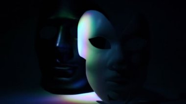 Pair theatrical masks black and white lit by color light — Stok video