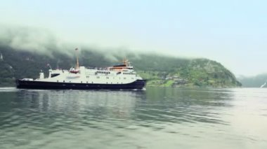 Passengers ship float in fiord at background of coastal village — Stock Video