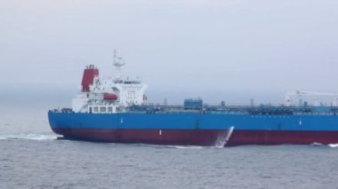 Back part of tanker floating on waves in cloudy weather — Stock Video