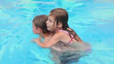 Little girl sits on her brother back and they swim in pool — Stock Video