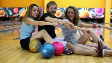 Boy and girls sit and simulate rowing on floor in bowling club — Stock Video