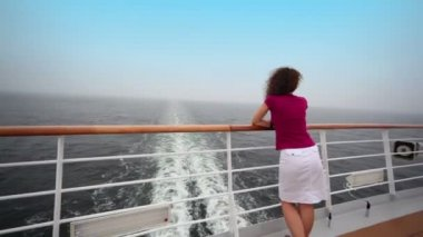 Woman stands on deck near fence and admire seascape — Stock Video