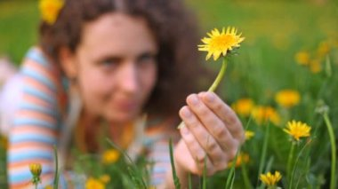 Young beautiful woman lies on lawn with dandelion in hand — Stock Video