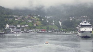 Rescue boat float on fiord to village and huge liner near shore — Stock Video