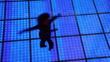 Woman spins in dance at dark discotheque with illuminated floor — Stock Video