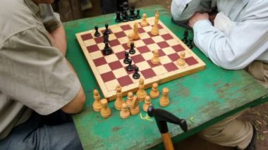 Two men sit and think under chessboard, closeup view of table — Stock Video