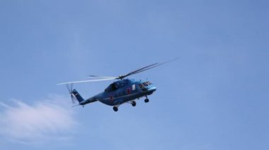 Helicopter quickly flies in blue sky in afternoon above ground — Stock Video