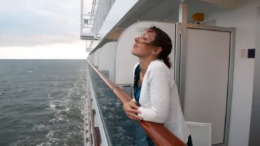 Woman stands at handrail looks at waves from board of ship — 图库视频影像