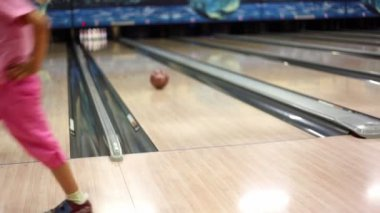 Little girl in pink clothes throws bowling ball and walks away — Vídeo Stock