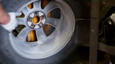Man rotates car wheel and shrink tyre by special tool — Stock Video