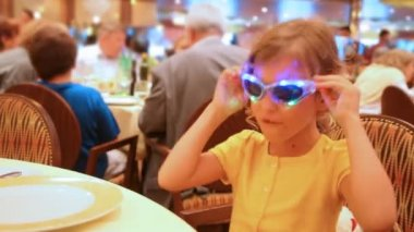 Girl behind table at restaurant wearing spectacles — Stock Video
