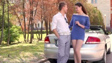 Young couple stand near cabriolet with rear light blink — Stock Video