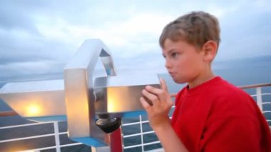 Boy looks in stationary field-glass afar from ship deck close up — Stock Video