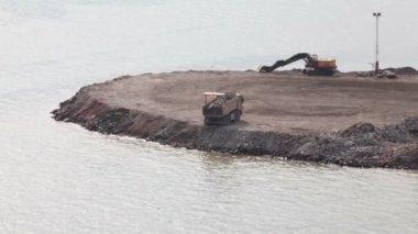 на строительной площадке на берегу работают грузовик выгружает и экскаватор — Стоковое видео