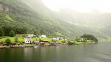 Mountains with waterfalls and small houses on banks of fiord — Stock Video