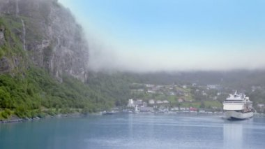 Fiord with huge liner near coastal village under mountain — Stock Video