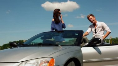 Girl stand in cabriolet with her boyfriend sit near and laugh — Stock Video