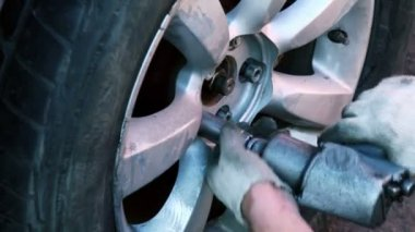 Man turn on wheel nuts with automatic tool, closeup view — Stock Video
