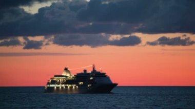 Výletní loď s osvětlení plave v moři při východu slunce — Stock video