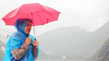 Woman under umbrella freezes against rocky landscapes — Vidéo