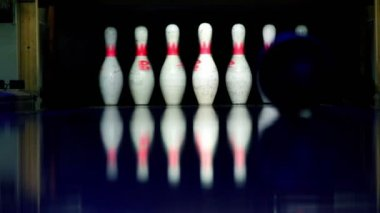 Ball rolls and beats skittles at bowling lane lit in dark — Stock Video