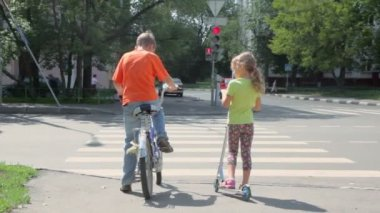 Boy sits on bicycle and his sister stands at pedestrian crossing — Stock Video