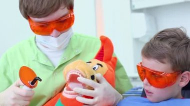 Dentist uses light for harden filling for jaw of toy near boy — Stock Video
