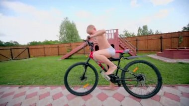 Boy in underpants ride on bike by road at homestead — Stock Video
