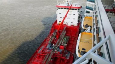 Cranes and workers on board of industrial ship near liner — Vídeo de stock