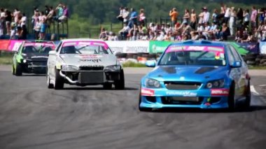 Racing cars enter into turn in front of tribunes with audience — Stock Video