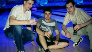Three friends sit and drink bear in dark bowling club — Vídeo de Stock