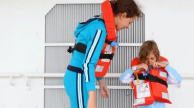 Mother helps daughter to fasten rope of life jacket on ship deck — Stock Video