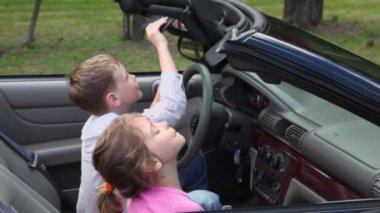Two kids play with mirrors in cabriolet, closeup view — Stock Video